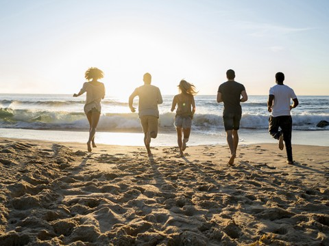 Friends running towards the sea at the beach